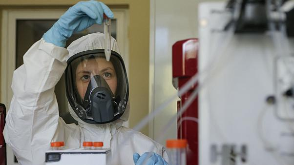 Thursday, Aug. 6, 2020, and provided by Russian Direct Investment Fund, an employee shows a new vaccine at the Nikolai Gamaleya