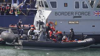 A UK Border Force vessel brings a group of people thought to be migrants into the port city of Dover, England, from small boats, Saturday Aug. 8, 2020.