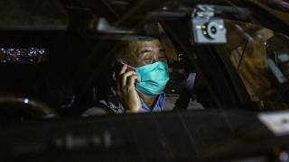 Hong Kong pro-democracy media mogul Jimmy Lai speaks on the phone after being released on bail from the Mong Kok police station.