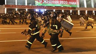 Police run to block demonstrators during a rally after the Belarusian presidential election in Minsk, Belarus, late Sunday, Aug. 9, 2020.
