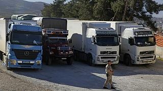 In this Oct. 31, 2018 photo, a Lebanese customs officer walks past trucks waiting to cross into Syria from the Lebanese border crossing point of al-Masnaa