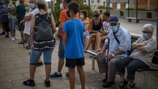 Varias personas esperan para hacerse una prueba PCR en Santa Coloma de Gramanet en Barcelona, España