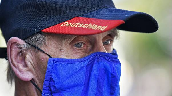 A man wears a face mask in the colours of the German first division soccer team FC Schalke 04. Gelsenkirchen, Germany, Wednesday, Aug. 12, 2020.