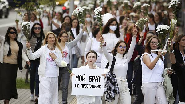 """Belarusian women, one with a poster reading """"My brother is not a criminal"""", rally in solidarity with protesters caught up in the state post-election crackdown, Minsk, Aug. 13."""