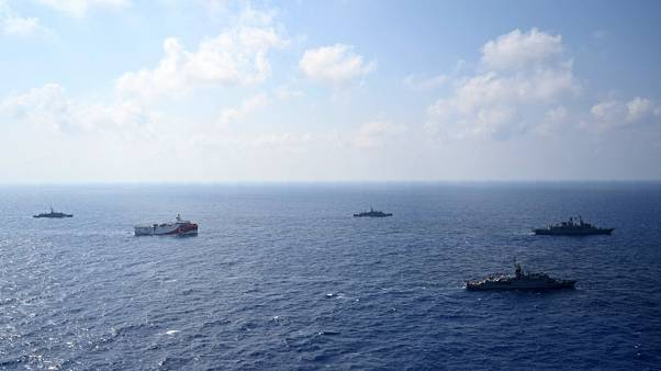 In this photo provided by the Turkish Defense Ministry, Turkey's research vessel, Oruc Reis, in red and white, is surrounded by Turkish navy vessel