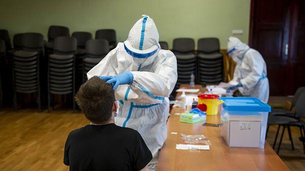 Mintát vesznek egy fiú garatnyálkahártyájáról koronavírusteszthez a Debreceni Egyetem mintavételi pontján 2020. május 14-én