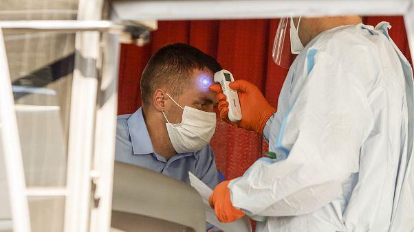 سائق يتم قياس درجة حرارة جسمه داخل حافلة قادمة من رومانيا إلى إيطاليا
