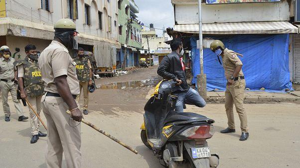 شرطي يضرب سائق دراجة لانتهاكه أوامر منع التجمهر بعد يوم من احتجاجات عنيفة في بنغالورو ، الهند
