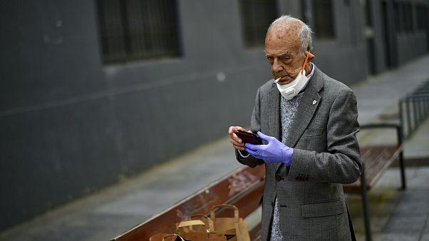 Un hombre fuma quitándose la mascarilla en España