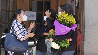 Women outside a funeral home where the body of Benoît Maria was brought