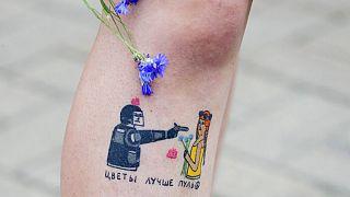 Tetoválás egy tüntetőn. A felirat nagyjából azt jelenti, hogy a virágok jobbak a töltényeknél