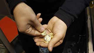 An Iranian goldsmith counts his gold coins at a gold market in the main old Bazaar of Tehran, Iran