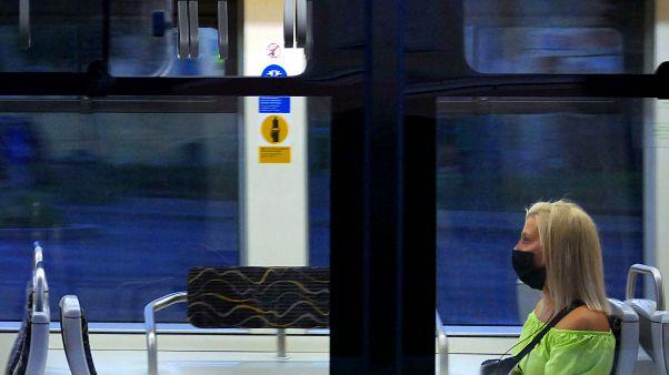 Védőmaszkot viselő és a javasolt távolságtartással elhelyezkedő fiatal utas a Budapesti Közlekedési Központ egyik villamosán