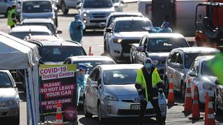 Cars queue at a COVID-19 test centre in Auckland, New Zealand