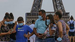 A Italian tourist family wearing a masks to prevent the spread of COVID-19 gather at Trocadero plaza near Eiffel Tower in Paris