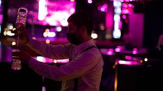 A waiter wearing a face mask to prevent the spread of coronavirus works in a discotheque in Madrid, Spain, early Saturday, July 25, 2020