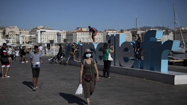 A woman walks along Marseille's Old Port, southern France, Friday Aug 7, 2020.