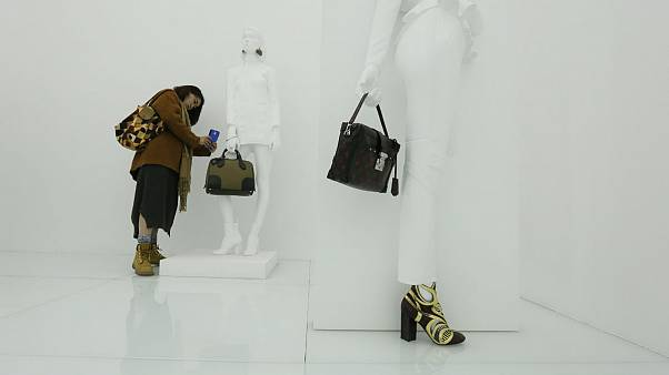 A visitor takes photo of a bag at an exhibition by french luxury brand Louis Vutton in Beijing