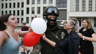 Mujeres abrazan a un soldado que vigila el edificio del Gobierno en Minsk en una protesta pacífica conra la represión policial