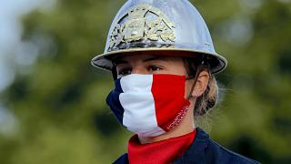 a firefighter wears a face mask with the colors of the French flag, prior to the Bastille Day parade