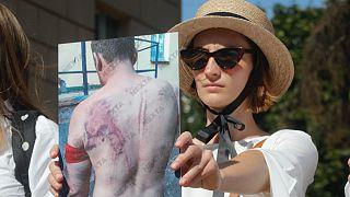 Belarus'un başkenti Minsk'te bir kadın protestolar sırasında polis şiddetine uğradığını iddia ettiği arkadaşının fotoğrafını gösteriyor