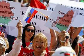 Supporters of Belarusian President Lukashenko hold posters that read: