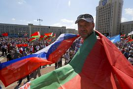 A man covers himself with Belarusian and Russian national flags as supporters of Belarusian President Alexander Lukashenko gather at Independence Square of Minsk, Belarus