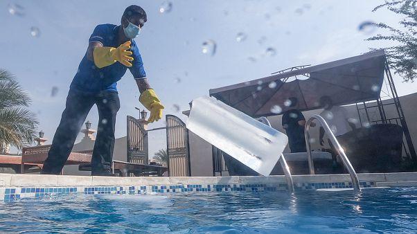 BAE sakinleri, yüzme havuzlarını büyük buz kütleleri ile serinletiyor