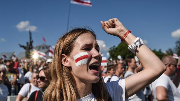 A woman Belarus opposition supporter with a drawing of a former white-red-white flag of Belarus used in opposition to the government punches the air.