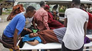 People help a civilian woman, who was wounded when a powerful car bomb blew off the security gates to the Elite Hotel, in Somalia Sunday, Aug. 16, 2020.