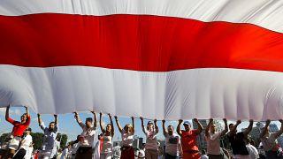 Opositores hacen ondear una bandera en Minsk, Bielorrusia