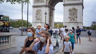 A family wearing protective face masks walk along on the Champs Elysee avenue, with Arc de Triomphe in background, in Paris, Saturday, Aug. 15, 2020.