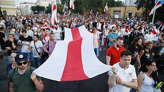 People carry an old Belarusian national flag during an opposition rally in Minsk, Belarus, Monday, Aug. 17, 2020