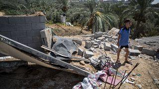 طفل فلسطيني يقف على أنقاض بيته المهدم بسبب القصف الإسرائيلي