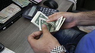 A currency exchange bureau worker counts U.S. dollars in downtown Tehran, Iran