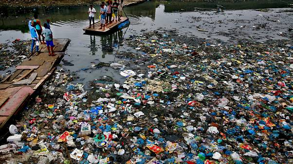 Oct. 2, 2016 file photo: a man guides a raft through a polluted canal littered with plastic bags and other garbage in Mumbai, India.