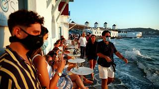 People, some of them wearing face masks against the spread of the new coronavirus, gather on Mykonos, Greece, Sunday, Aug. 16, 2020.