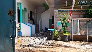 In this photo provided by the Philippine Red Cross, debris are scattered at a house after a quake struck in Cataingan, Masbate province, central Philippines.