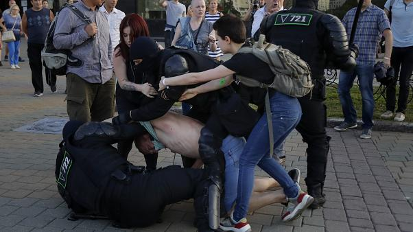 La policía detiene a un manifestante mientras dos mujeres tratan de defenderlo durante una manifestación contra las disputadas elecciones presidenciales en Minsk, Bielorrusia.