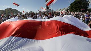 Opposition supporters wave an old Belarusian national flag at a rally in Minsk on Sunday.