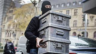 Police carry boxes after investigations at a jeweler in Duisburg-Marxloh, western Germany
