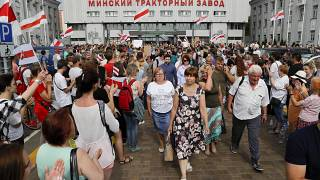 Workers leave the Minsk Tractor Works at the end of a shift on Tuesday, applauded by opposition workers