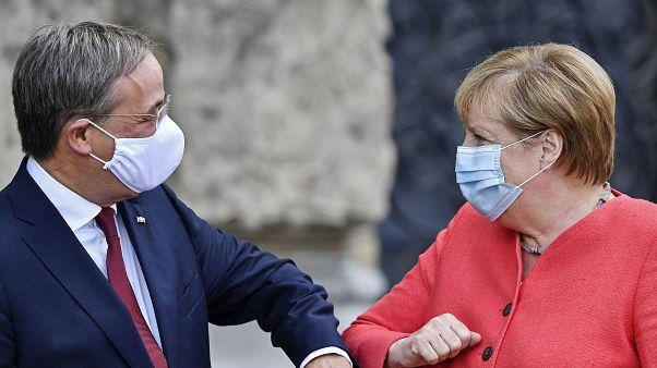 Канцлер Германии Ангела Меркель здоровается с премьер-министром федеральной земли Северный Рейн-Вестфалия.
