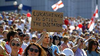 """Belarus'un başkenti Minsk'te düzenlenen gösteride bir eylemci, """"Lukaşenko hala diktatör"""" yazılı pankart taşıdı"""