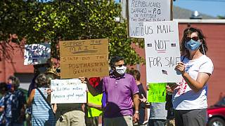 gather in front of the United States Post Office to protest recent changes to the USPS under new Postmaster General Louis DeJoy, Tuesday, Aug. 11, 2020 in Midland, Michigan