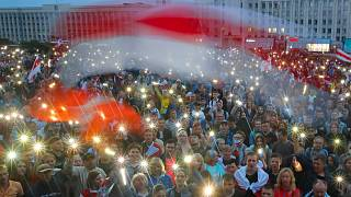 Belarusian opposition supporters light phones lights and wave an old Belarusian national flags during a protest rally in front of the government building Wednesday, Aug. 19, .