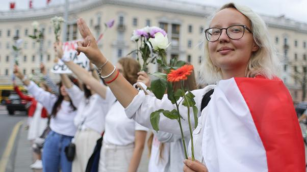 Belarusians protesting against disputed presidential elections results hold flowers and flash victory signs during a protest in Victory Square in Minsk, Belarus. August 20