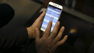 An Iranian shareholder monitors stock prices on his mobile phone at the Tehran Stock Exchange in Tehran, Iran