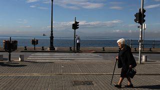 Elderly people walk along a coastal avenue in the northern Greek port city of Thessaloniki.