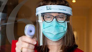 Avustralya'nın Melbörn kentinde bir sağlık çalışanı insanların koronavirüs olup olmadıklarını anlamak için vücud ısılarını ölçüyor